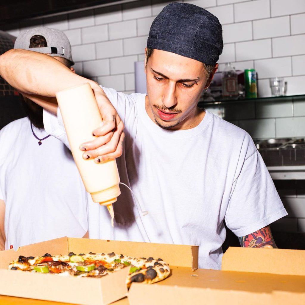 Gordo's Pizzeria chef putting finishing touches on freshly baked pizza