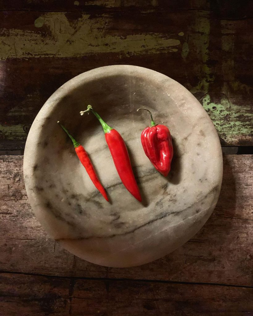 Wooden bowl holding chili peppers